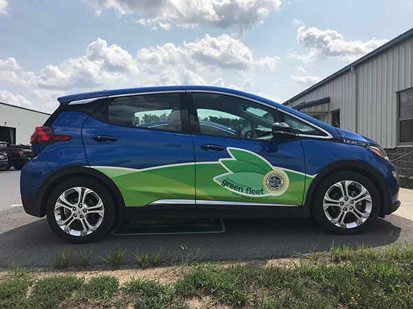 All electric vehicle, Chevrolet Bolt, with Monroe County Green Fleet logo on door