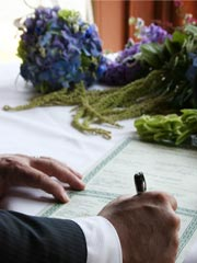 Picture of groom signing marriage certificate.