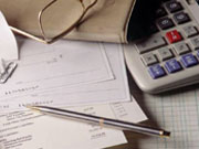 Picture of checks and paperwork by calculator on table.