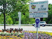Picture of flowers underneath Monroe County In Bloom sign.