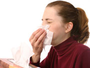 Picture of woman covering mouth as she coughs.