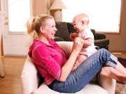 Picture of smiling mom with baby in living room.