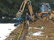 Picture of a contractor is shown installing an Individual Sewage Treatment System.