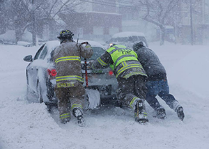 An image of three fire fighters pushing a car in a foot of snow during a snowstorm.