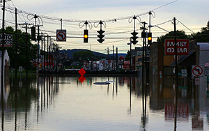 An image of a flooded street with water reaching halfway up houses and a traffic light with the yellow light lit up.