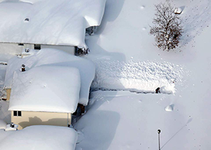 An aerial view of houses covered in snow and a person shoveling out a path when the snow is taller than them.