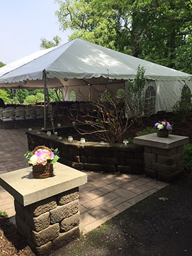 Outdoor area near Clubhouse with tent set up over chairs for wedding or similar event